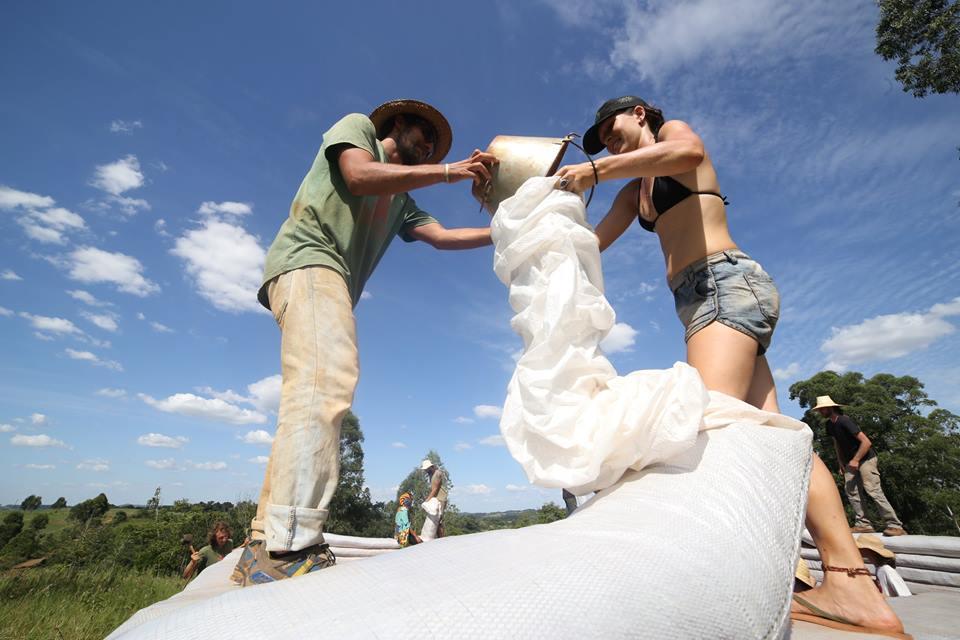 Open de terra, sacas e baldes. Bioconstrutores colocando terra nas sacas.