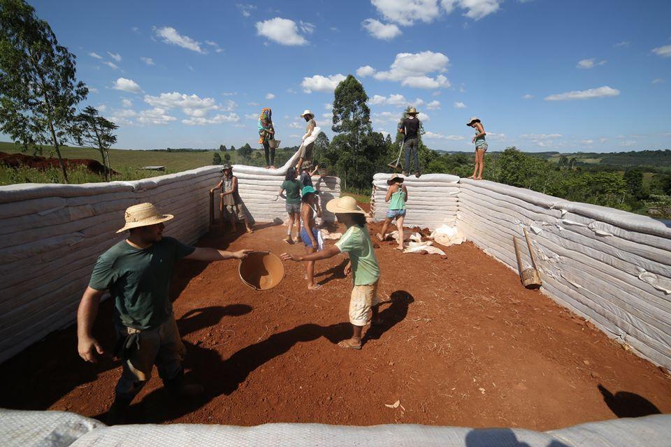 """De baldinho em baldinho de terra se erguem essas bonitas paredes na técnica do """"superadobe"""": terra ensacada a rodo!"""